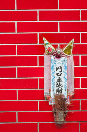 Small shrine to the earth god Tu Di mounted on a red tiled wall in Hong Kong
