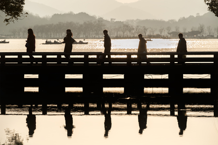 Five tourists in silhouette cross a bridge at Hangzhou's West Lake scenic area