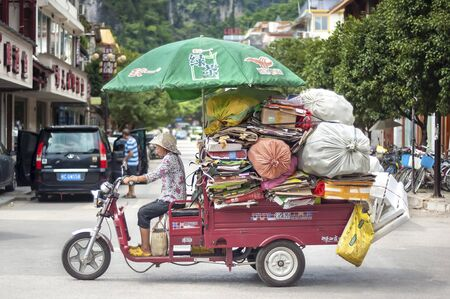 YANGSHUO, CHINA - AUG 10, 2013 - Small truck overloaded with cardboard and bags of plastic bottles in the Southwestern town of Yangshuo, China Editorial