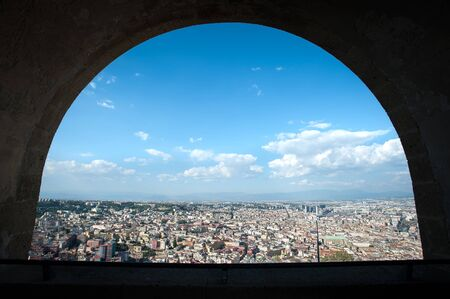 View of the Naples cityscape through an arch of Castel Sant'Elmo, Italy. On the left of the shot can be seen the long, straight Spaccanapoli street.