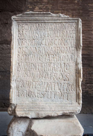 Ancient marble tablet engraved with the Venantius incription inside the Colosseum in Rome, Italy. The inscription commemorates the restoration of the Colosseum's podium and arena, at his own expense, by Decius Marius Venantius Basilius after an earthquake