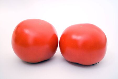 macrophotography: two red tomatos over white background, macrophotography