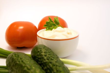 mayonnaise with tomatos, leeks and cucumbers over white background photo