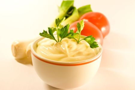mayonnaise in sause-boat with parsley twig over white background photo