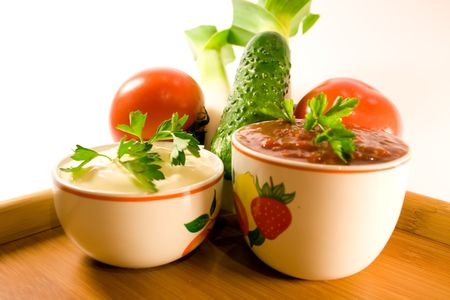 mayonnaise and ketchup in sause-boat with parsley twig and fresh vegetables photo