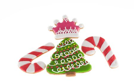 christmas crown: Christmas cookies xmas tree, two canes and pink crown over white background