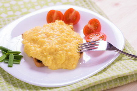 huevos revueltos: French style scrambled eggs on toast with tomatoes Foto de archivo
