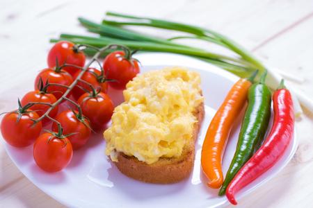 huevos revueltos: estilo Inglés huevos revueltos sobre una tostada con verduras Foto de archivo