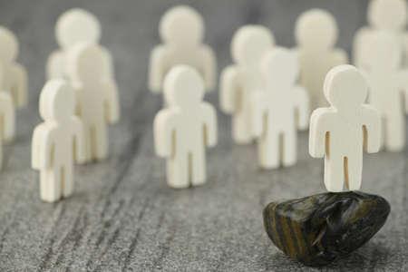 Gruppe von Holzfiguren und eine Figur im Vordergrund als Modell oder Lautsprechern, kann in Network Marketing Standard-Bild