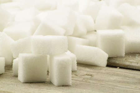 diabetes: Many pieces of sugar cubes in front of wood background