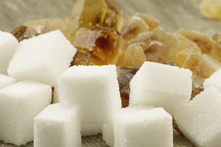 emphasized: Heap of brown sugar candy and white sugar cubes