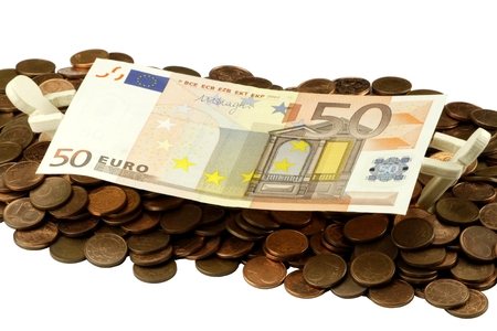 business competition: 50 Euro bill with cent coins and wooden figures Stock Photo