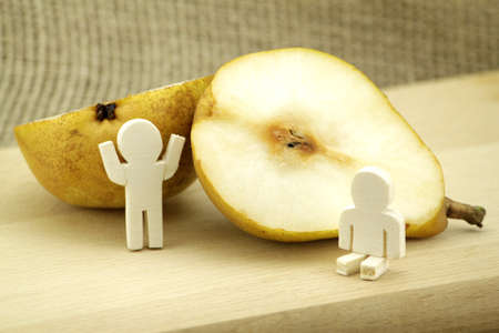 halved: Halved pear decorated with two wooden males Stock Photo