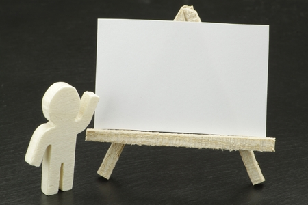 wooden figure: A wooden figure in front of a white canvas for your text Stock Photo
