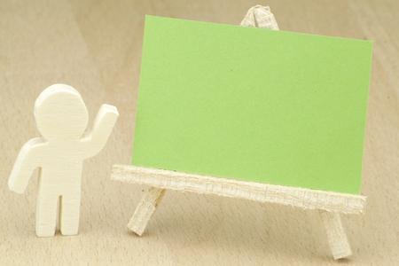 緑の黒板で、木彫りの像を提示 写真素材