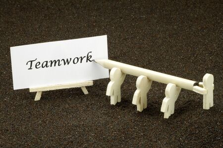 mlm: Wood males Jointly write the word Teamwork Stock Photo