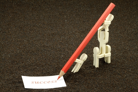 Acrobatic figures of wood write the word Success Stock Photo