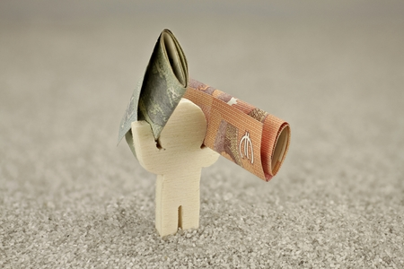 miserly: Small wooden figure carries two banknotes on the shoulders