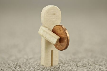 help each other: Wooden figure hands a cent - every donation counts