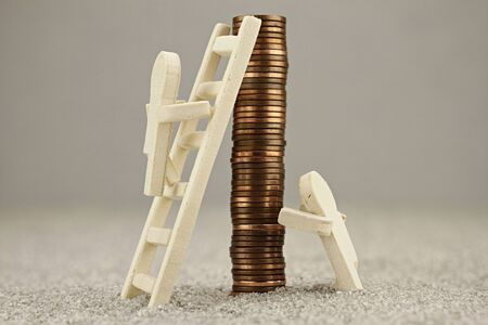 Little wooden one rises on a coin pile with a ladder