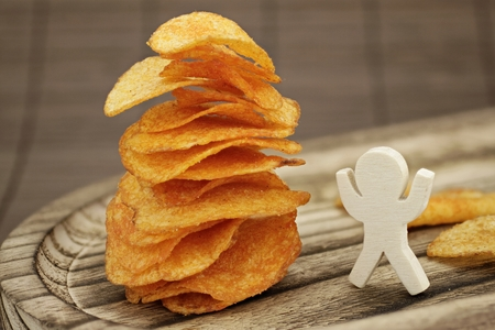 Wooden male enjoys a large stack of potato chips