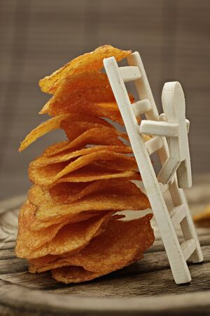Wooden male with a ladder on a large stack of delicious potato chips