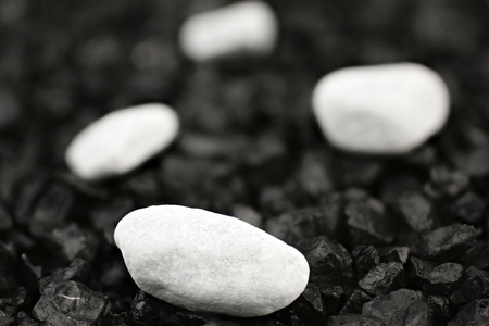 White pebbles in front of black background with black grit Stock Photo