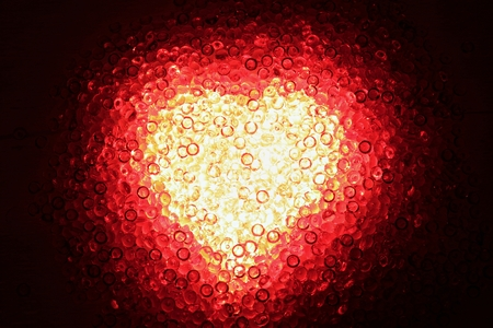 Shining heart of red decoration stones against a dark background Stock Photo