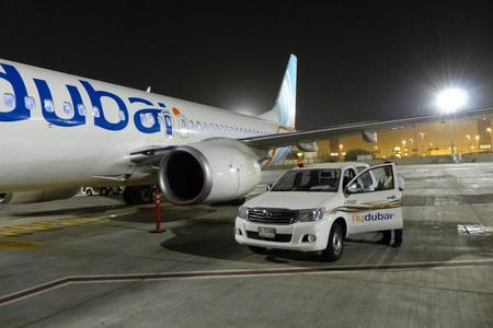 Dubai International Airport, United Arab Emirates, september 4, 2015: Airplane and car of Fly dubai company on the runway
