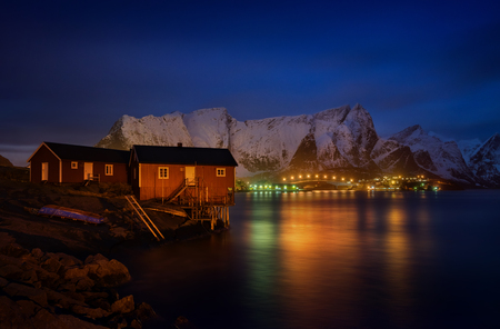 rorbu: Rorbu in Reine at night with mountains and illuminated bridge in background, Lofoten Stock Photo