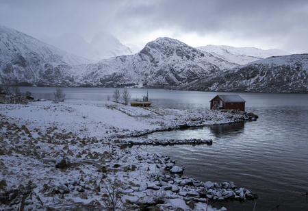 rorbu: Rorbu and little boat in harbor among snowy mountains, Lofoten