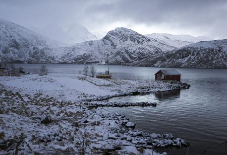 montañas nevadas: Rorbu y pequeño barco en puerto entre montañas nevadas, Lofoten