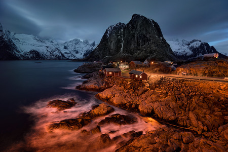 rorbu: Cloudy blue night with illumiated red rorbu of Hamn�y village, Lofoten Stock Photo