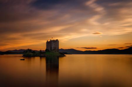 Stalker Castle reflection in orange sunset light, Highlands, Scotland