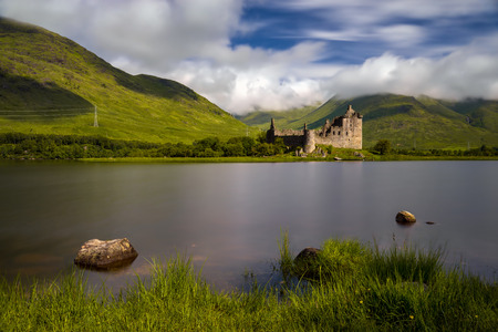 Stones in Loch Awe with Kilchurn Castle an mountains in background, Highlands, Scotland 免版税图像