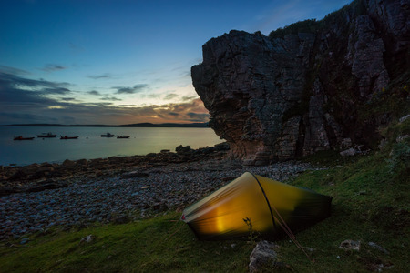 Tent pitched on Elgol coastline at sunset with boats and mountains in background, Isle of Skye, Scotland