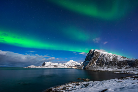 northern light: Aurora Borealis over Offersoykamen summit at Flaget coastline, Lofoten Stock Photo
