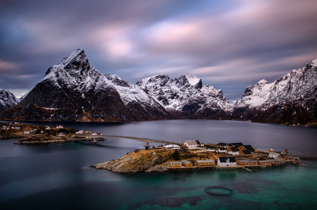 Sakrisoy island with rorbu at Reinefjorden with snowy mountains in background, Lofoten