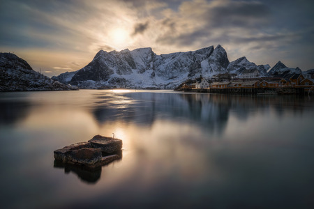 Sakrisoy island and Reine village at sunset with a cold snowy mountains in background, Lofoten