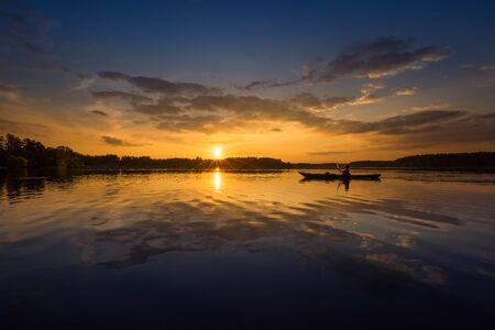 Reflections of lonely kayaker on Zdrozno Lake at Mazuras Lakeland in sunset, Poland