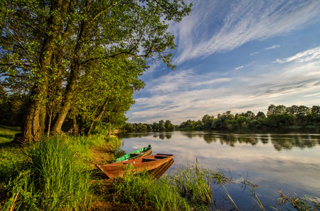 narew: Two wooden boats on river Narew in sunset, Poland