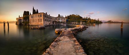 Punta San Vigilio harbour at Garda Lake with mountains in background, Italy