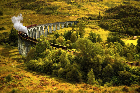 Jacobite steam train on old viaduct in Glenfinnan, Scotland