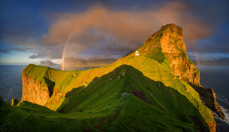 Kalsoy island and Kallur lighthouse with rainbows in sunset light, Faroe Islands Stockfoto