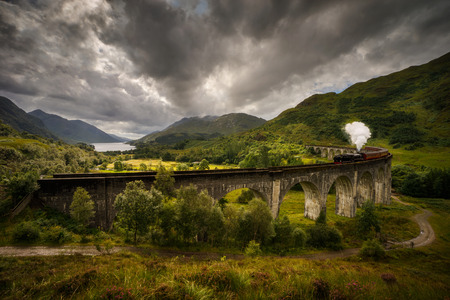 Jacobite steam train on old viaduct in Glenfinnan with mountains and Loch Shiel in background, Scotland