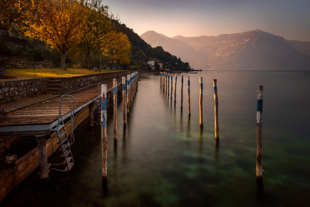 Little harbour on Iseo Lake with mountains in background, Italy