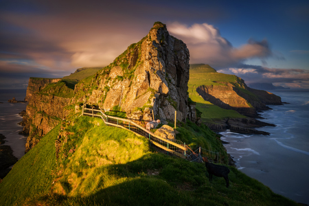 Tourist path on Mykines ridge in sunset, Faroe Islands Imagens