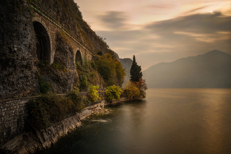 Bike road around Iseo Lake under railroad bridge, Italy  Фото со стока