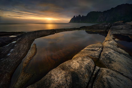 Tugeneset rocky coast with mountains in background at sunset, Senja, Norway