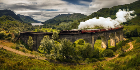 Panorama of Jacobite steam train on old bridge, Scotland